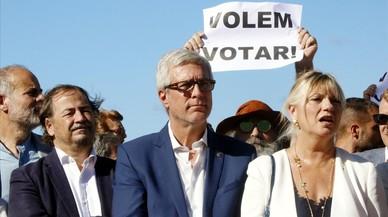 """El alcalde de Tarragona,Josep Felix Ballesteros, con los regidoresPau Perez y Elvira Ferrandoante unapancarta de""""Volem votar""""."""
