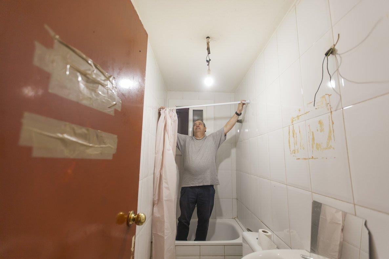 Alfonso Fernández coloca unas cortinas de ducha en el baño de los Amaya.