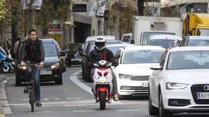 Una bici, una motoy coches, en la calle de Balmes, antes de cruzar la Diagonal.