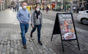 Dos personas con mascarillas por temor al coronavirus en el centro de Madrid.