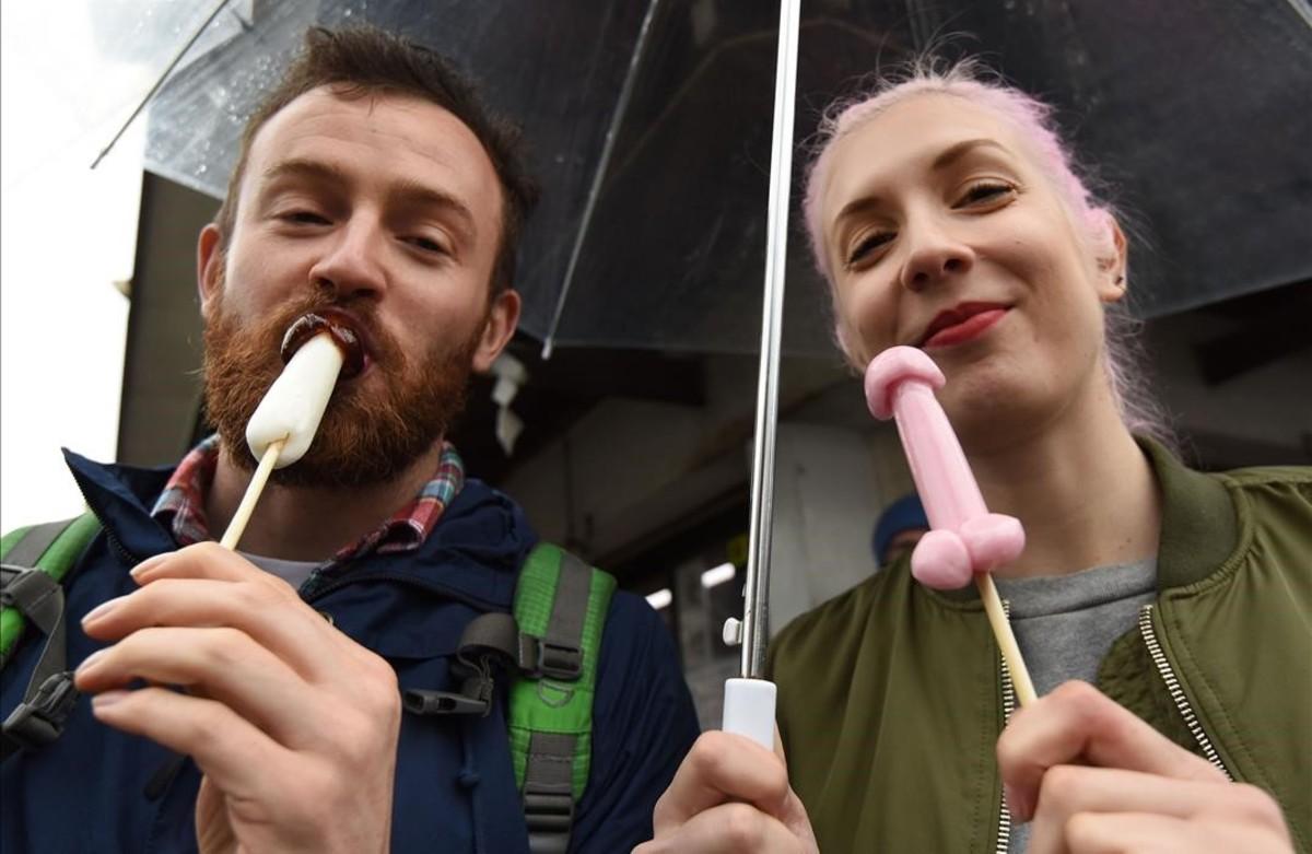 Una pareja come helados con forma de pene durante el desfile.