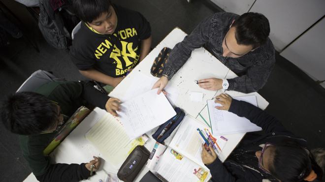 Un grup de nens fan els deures amb lajuda de voluntaris al Casal dInfants del Raval.