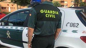 Un guardia civil, junto a un coche del instituto armado.