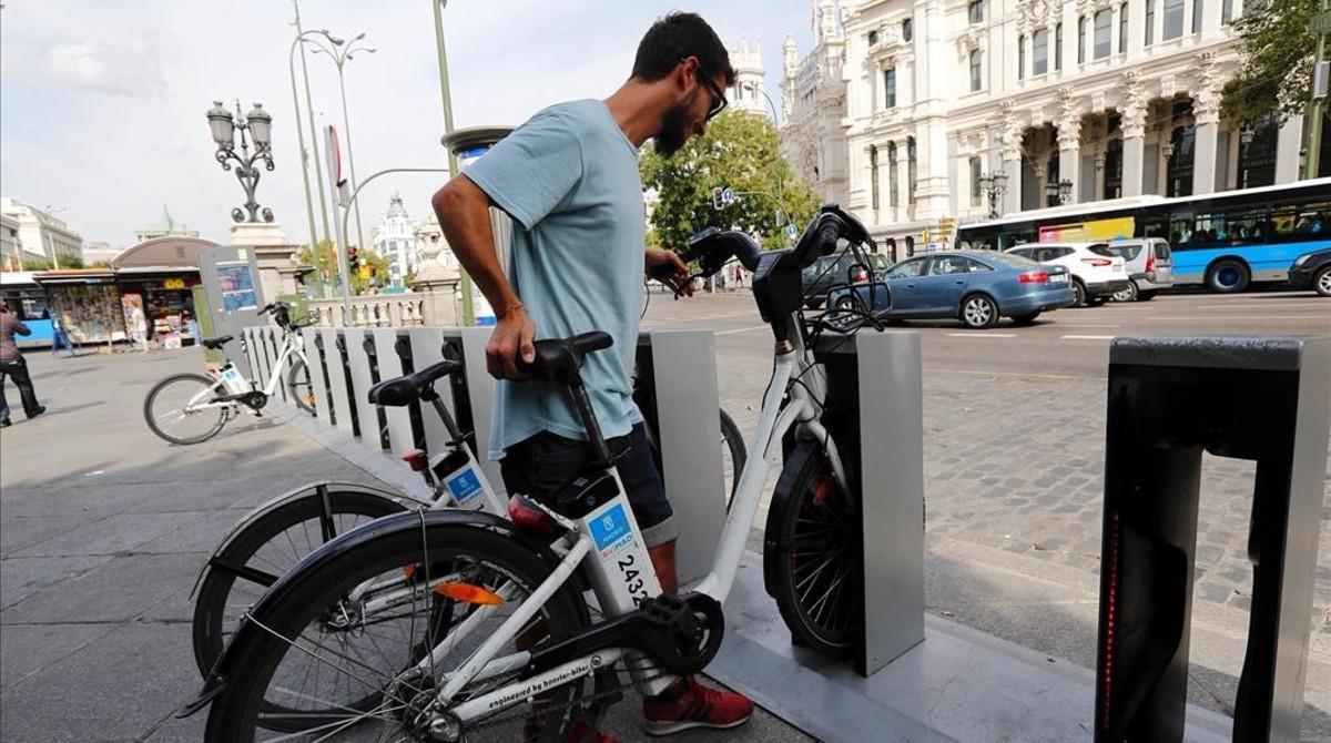 Un usuario aparca en una de las estaciones de BiciMAD.