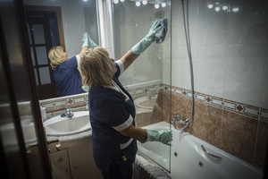 Una mujer de limpieza en un hogar realizando sus labores profesionales.