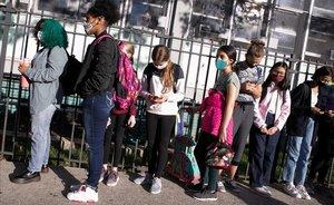 Los estudiantes de un colegio de Brooklyn esperan en fila para someterse a un control de temperatura el primer día de reapertura de la escuela.