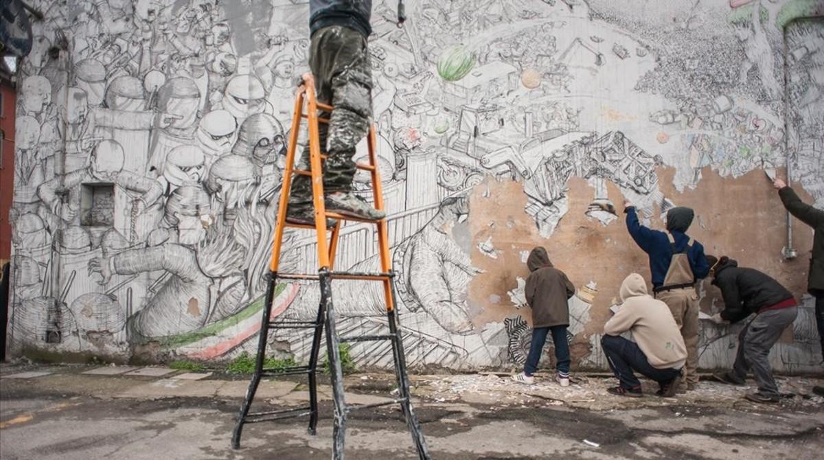 Blumuestra su contundente respuesta a la exposición de arte urbano: varias personasarrancanuno de sus murales en Bolonia.