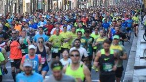Miles de corredores del maratón a su paso por la carretera de Sants.