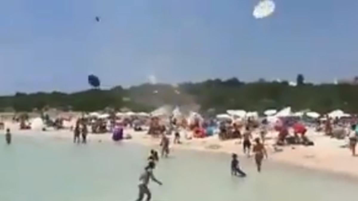 Momento en el que el remolino ha comenzado a levantar sombrillas en la playa de Binibeca (Menorca).