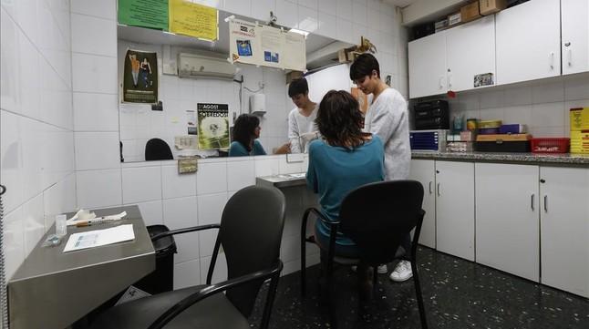 Una sanitaria atiende a una mujer en un sala de venopunción de Barcelona, este martes.