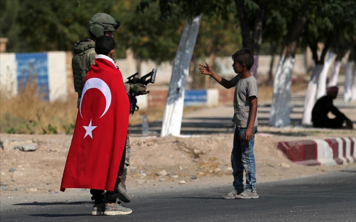 Un niño con una bandera de Turquía camina junto a un soldado turco en la ciudad de Tal Abyad.