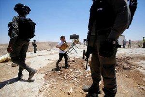 Un niño palestino pasa junto a soldados israelís camino de la escuela, cerca de Hebron.