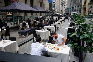 People eat at a mostly empty restaurant with tables on the street, in the financial district during the coronavirus disease (COVID-19) pandemic in the Manhattan borough of New York City, New York, U.S., September 9, 2020. Picture taken September 9, 2020. REUTERS/Carlo Allegri - RC2JWI9IBNGK