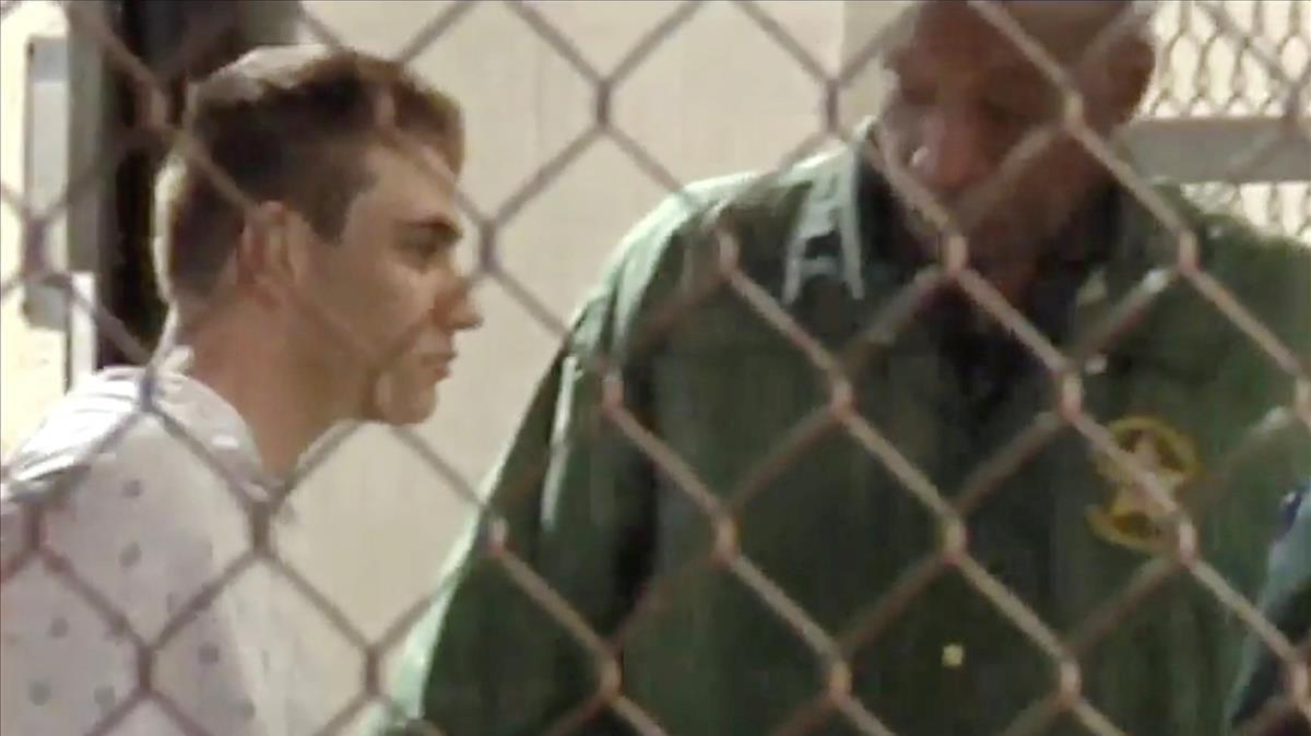 Un policía escolta a Nikolas Cruz (en una imagen de vídeo) en la cárcel del condado de Broward, tras el tiroteo en el instituto de Parkland (Florida), el 15 de febrero.