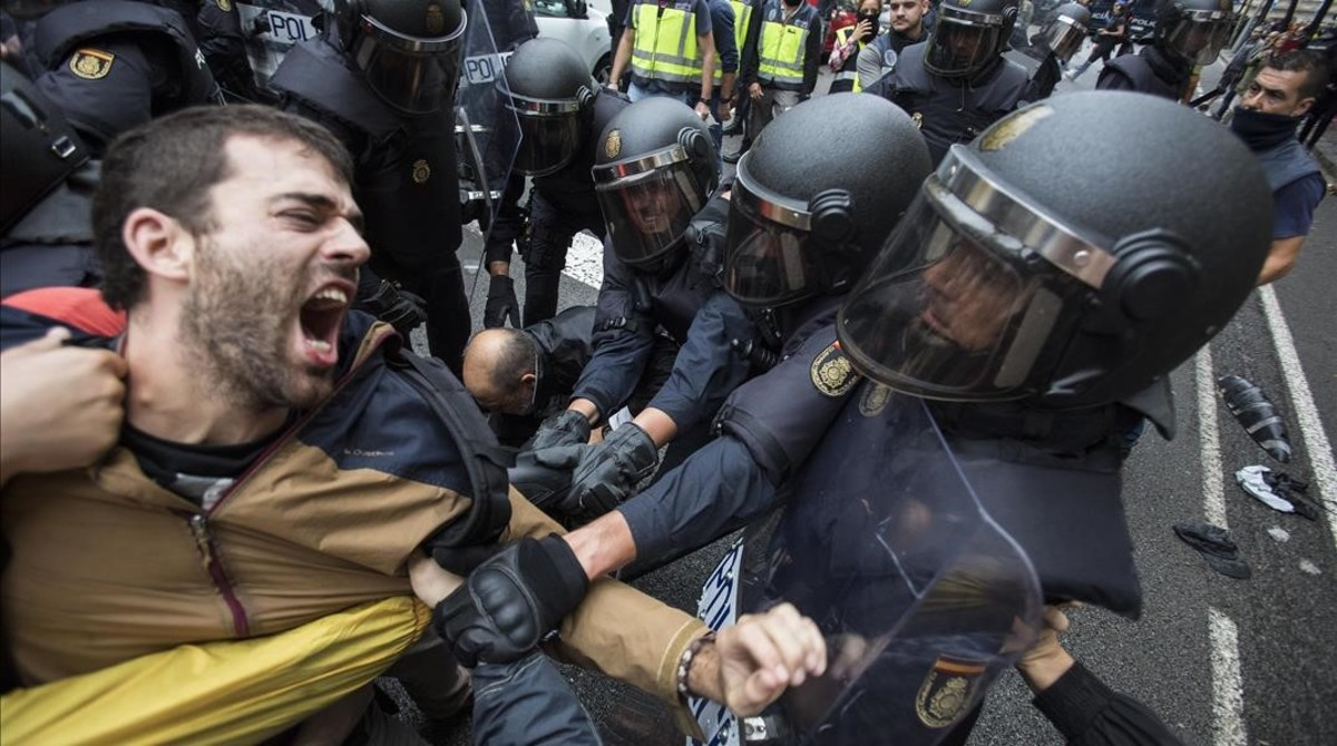 La policia nacional intenta desalojar a las personas concentradas en las puertas del colegio electoral Ramon Llull de Barcelona el 1-O.