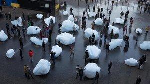 Público interactúa con pedazos de hielo fundiéndose en una exhibición islandesa y danesa en el Tate Modern en Londres.
