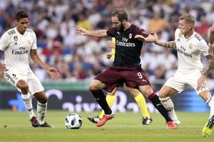 Higuaín (9), del Milán, controla un balón ante Kroos (d) y Varane.
