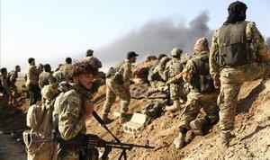 Rebeldes sirios respaldados por Turquía y soldados turcos observan las columnas de humo que se levantan desde la ciudad fronteriza de Ras al-Ain.