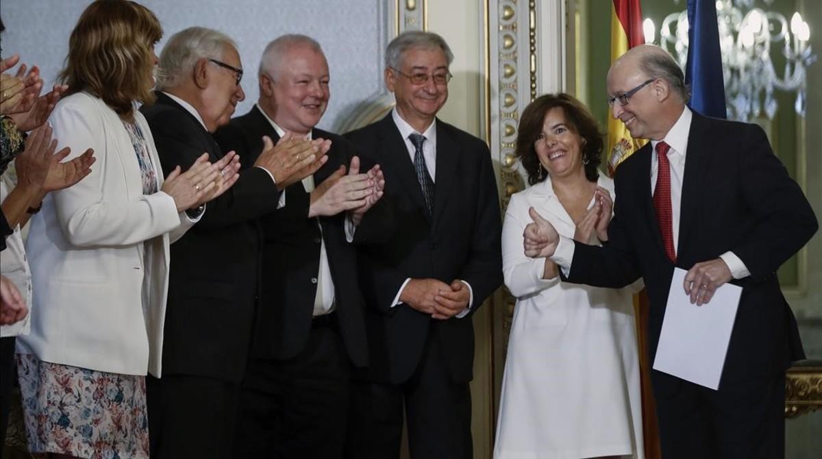 El ministro Cristóbal Montoro y la vicepresidenta Soraya Sáenz de Santamaría, la semana pasada, con los expertos que han elaborado el informe sobre la financiación autonómica.