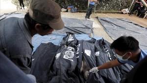 Un hombreinspeccionalos cuerpos sin vida de las víctimas de un corrimiento de tierra en una mina en el municipio de Itogon, Filipinas, tras el paso del tifón.
