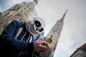 Tras una máscara, un usuario de Pokémon Go juega con la aplicación en las calles de Viena.