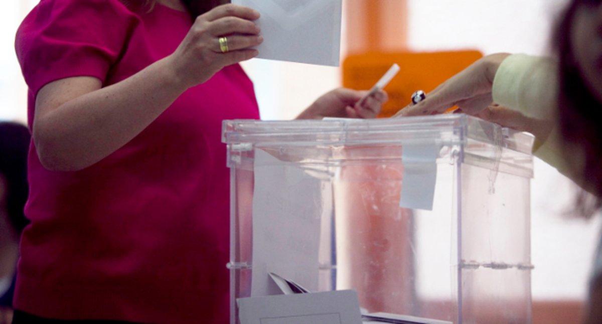 Una electora deposita su voto en la urna.