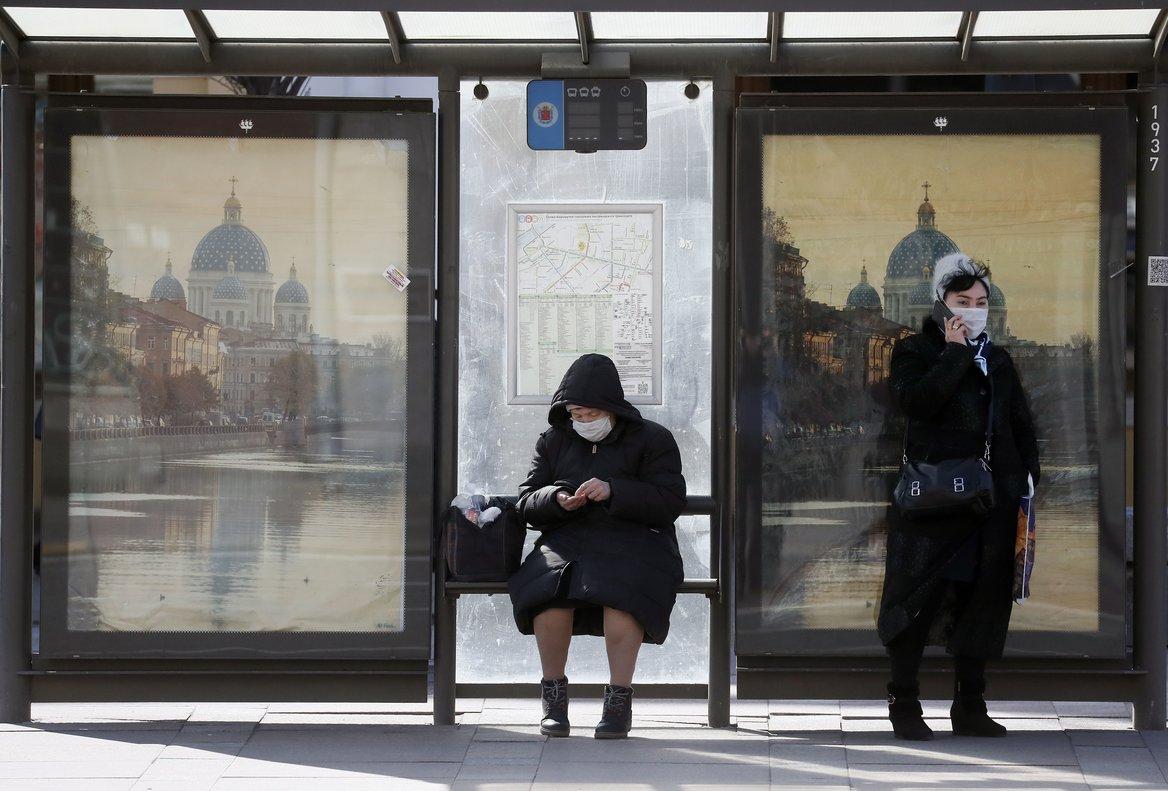 Unas mujeres con mascarillas en una parada de bus en San Petersburgo