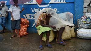 Unas mujeres se protegen de la lluvia con un plástico en la capital de Haití, Port-au-Prince.