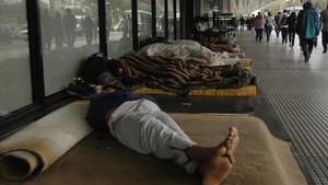 Varias personas duermen en la calle en Buenos Aires.