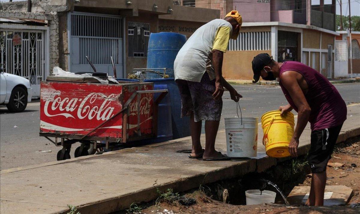 Venezolanos recogen agua en la ciudad de Maracaibo.