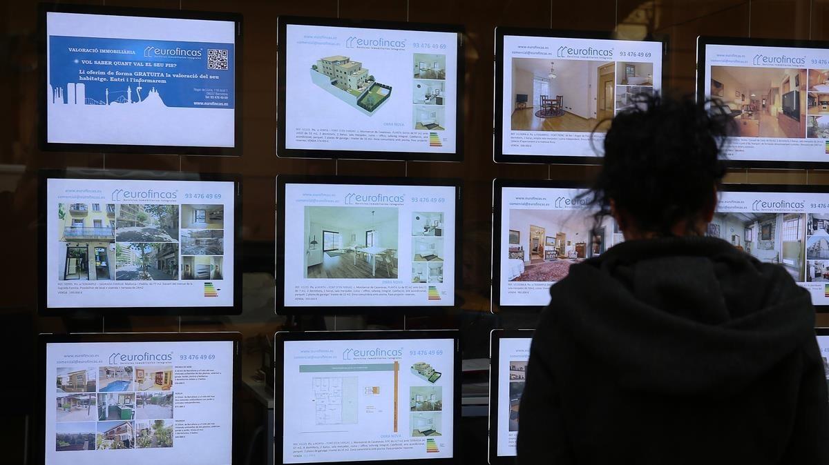 Ofertas de ventas de pisos en el escaparate de una inmobiliaria