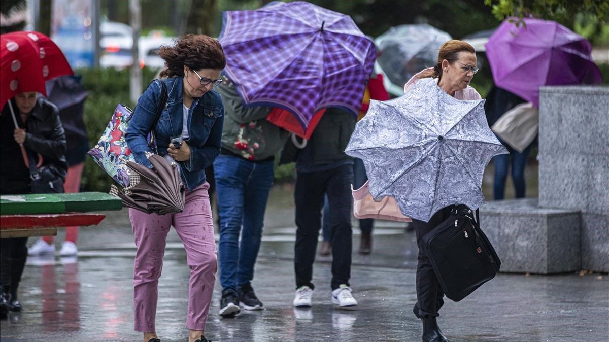 Varias personas se protegen de la lluvia en Valencia,donde se ha decretado alerta por lluvias torrenciales