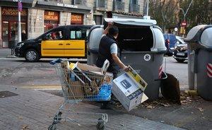Un hombre coloca residuos en un contenedor en Barcelona,a finales del 2019.