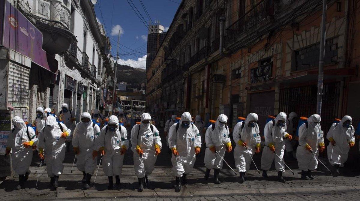 Trabajadores muncipales fumigan calles de La Paz, en Bolivia, contra el coronavirus.