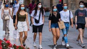 Jóvenes protegidos con mascarillas, paseando por el centro de Lleida.