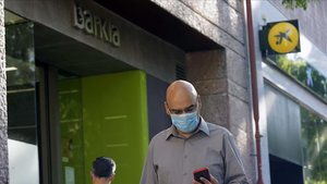 Un hombre camina delante de dos oficinas contiguas de Bankia y CaixaBank.