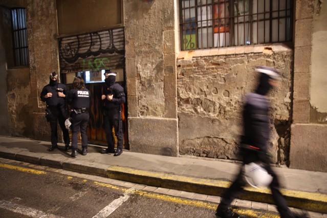 Varios agentes montan guardia ante uno de los locales registrados, en la calle Erasme del Raval.
