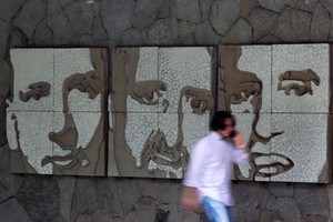 A man walks past portraits of three of the six murdered Jesuit priests, in San Salvador
