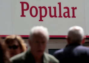 FILE PHOTO: People walk past a branch of Spains Banco Popular in Madrid