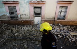 A firefighter walks in front of a house damaged during a 4 9 earthquake in ValenciaCarabobo StateVenezuelaon December 272018- A strong tremor followed by a score of aftershocks shook Caracas and several Venezuelan states earlyPhoto by JUAN CARLOS HERNANDEZAFP