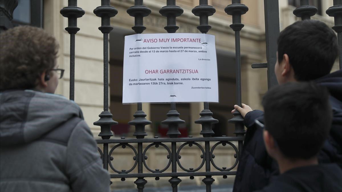 Alumnos de un colegio de Bilbao leen el comunicado del Gobierno vasco donde se cancelan las clases hasta el 27 de marzo, este jueves.