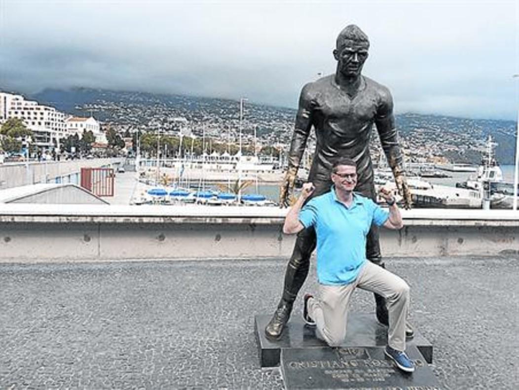 Un fan de CR7 se hace una foto junto a suestatua en Funchal, capital de Madeira.