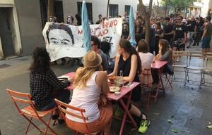 Paso de la cabecera de la manifestación junto a unos turistas en una terraza.