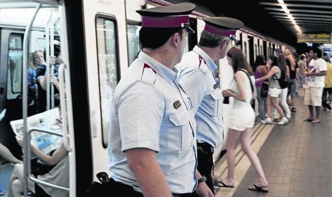 Dos mossos vigilan la entrada a los vagones del metro en busca de carteristas.