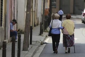 Dos mujeres mayores pasean por la calle.