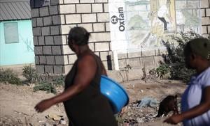 Dos mujeres pasan ante un mural de Oxfam en Puerto Príncipe, Haití.
