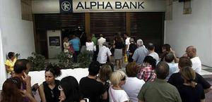 Desenes de persones fan cua per treure diners d'un banc a Atenes.