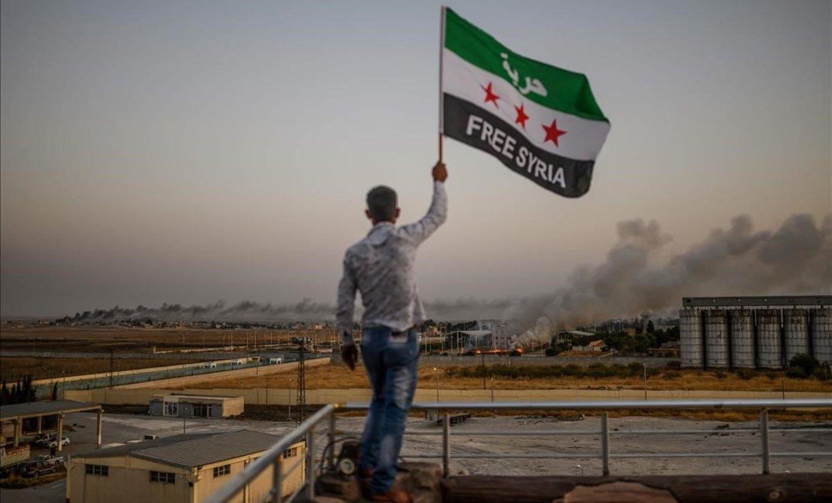 Un hombre sostiene una bandera en la que pide la liberación de Siria mientras las columnas de humo se elevan en las localidades fronterizas bombardeadas este domingo.