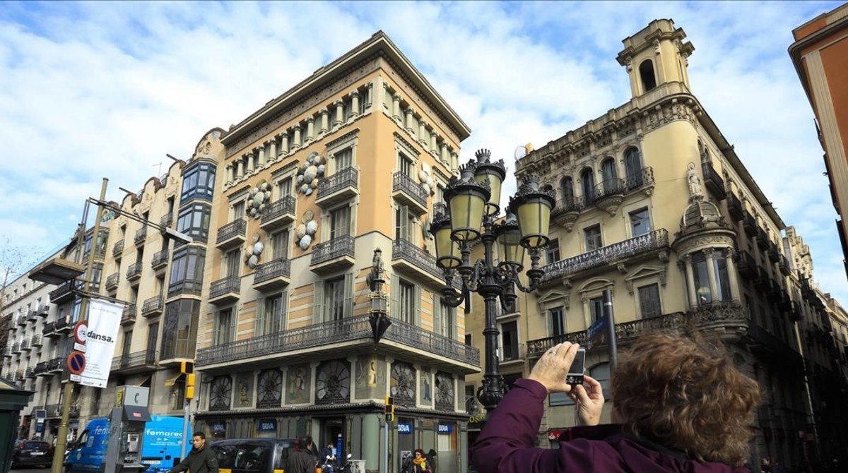 Una turista fotografía la Casa Bruno Cuadros, en la Rambla