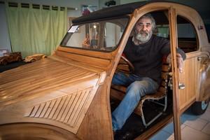 El carpintero jubilado francés Michel Robillard posa orgulloso dentro de su insólito Citroën 2CV de madera.